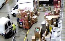Dos homes detinguts pels Mossos en una empresa de missatgeria obrint una furgoneta per carregar paquets.
