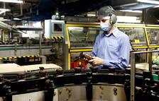 Un treballador inspecciona un pot de Nescafé al costat d'una de les línies de producció de la fàbrica de Girona.