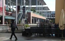 Un chico paseando por al lado de mesas y sillas retiradas en un punto del centro comercial La Maquinista.