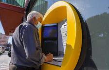 Una persona gran del barri de Sant Pere i Sant Pau fent gestions a través d'un caixer automàtic.
