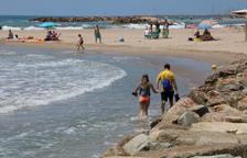 Una platja de Cunit sense sorra, amb dos banyistes creuant amb l'aigua als turmells.