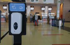 Un dispensador de gel hidroalcòholic a l'aeroport de Reus amb una cua de passatgers al fons facturant.