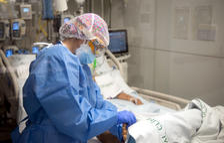 Una enfermera con un paciente ingresado en el Área de Vigilancia Intensiva.