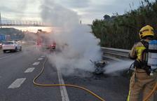 Imagen de Bombers apagando el vehículo incendiado.