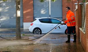 Un operario limpia con agua a presión una acera llena de hojas en el barrio de La Granja de Tarragona. Imagen del 6 de noviembre de 2018