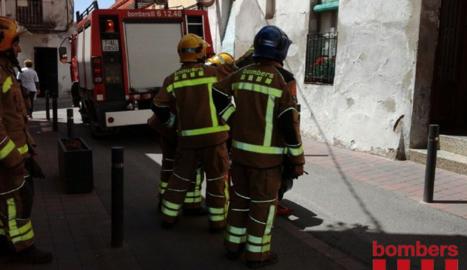 Los bomberos trabajando en el edificio donde ha tenido lugar el pequeño fuego.