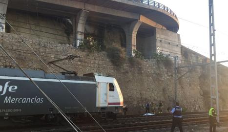 Al fons de la imatge es veu es cos de l'home, cobert, i al costat d'una màquina de tren.