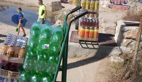 Botellas de refrescos de un repartidor sobre una arqueta y, a la derecha, aspecto que ofrece la valla metálica del ferrocarril.