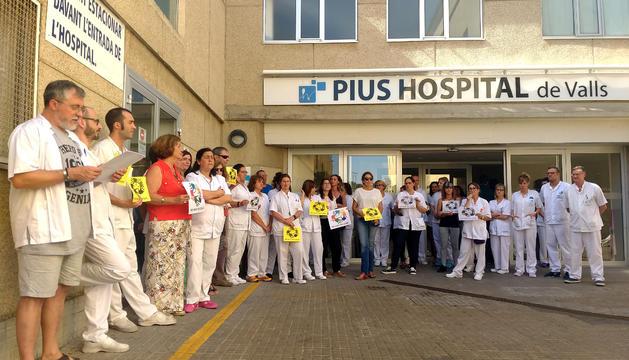 Una cuarentena de trabajadores del Pius Hospital de Valls leyendo un manifiesto de protesta delante del centro.