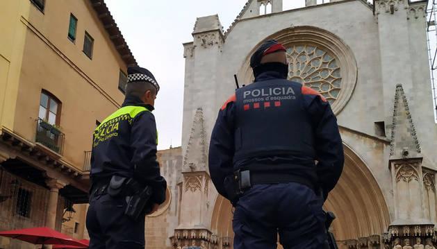 Dos agents, un de Mossos i un de Guàrdia Urbana, davant la Catedral.