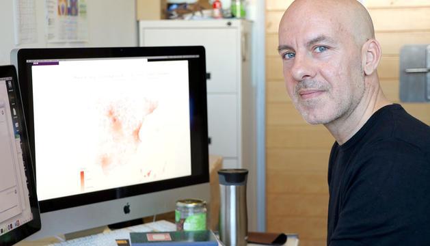Àlex Arenas, investigador del grup de recerca Alephsys Lab de la URV, amb una pantalla al fons amb el mapa de l'estat espanyol.