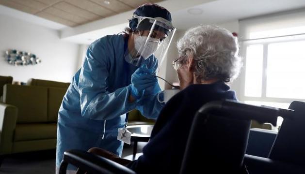 Una cuidadora dona de menjar a una anciana en una residència a Madrid.
