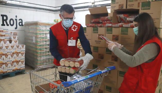 Dos voluntaris de Creu Roja Tarragona omplint el carro d'aliments per una persona en situació de vulnerabilitat.