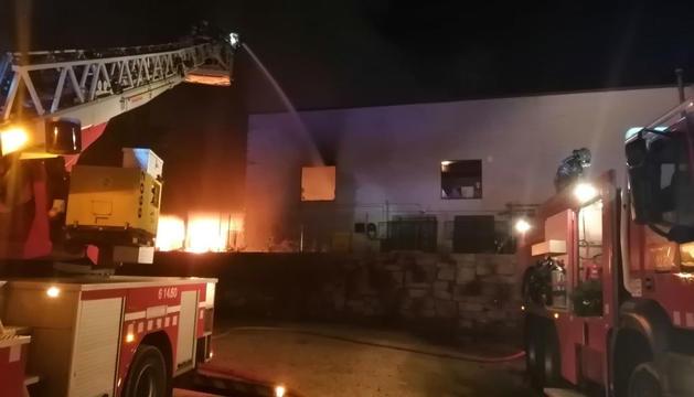 Imagen de los bomberos intentando apagar el fuego en la nave.