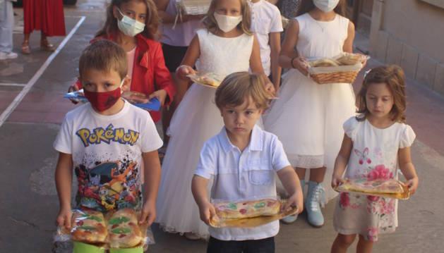Els nens que han fet la primera comunió duent les coques.